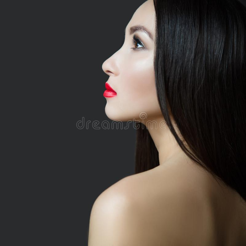 Young beautiful woman with red lipstick and perfect skin. Dark straight long hair royalty free stock images