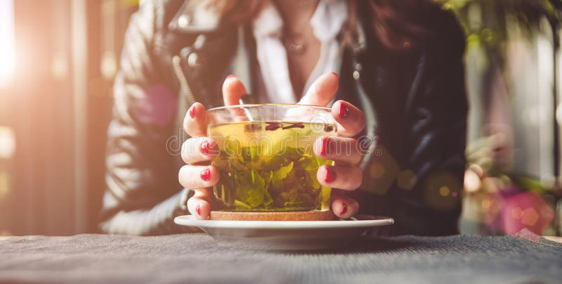 Young beautiful woman with red manicure drinking tea with herbs and lemon in cafe. Close up. royalty free stock photos
