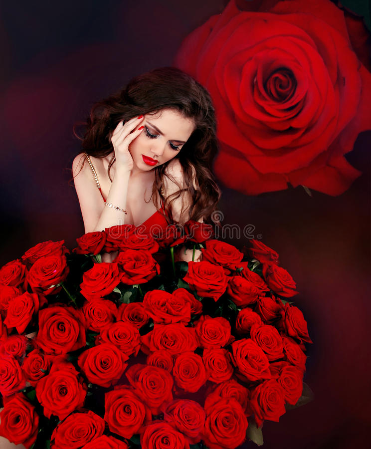Young beautiful woman with red roses bouquet over flowers. Studio stock photo