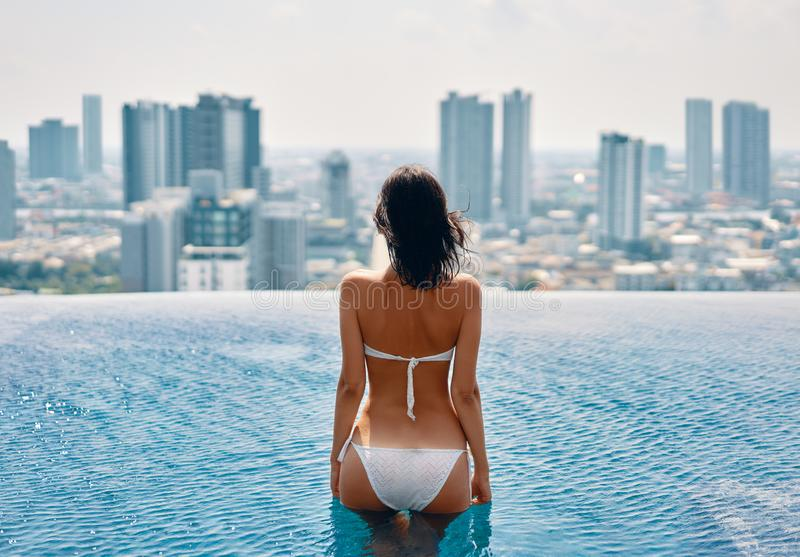 Young beautiful woman relax in swimming pool on rooftop and enjoy cityscape. Summer vacation concept royalty free stock image