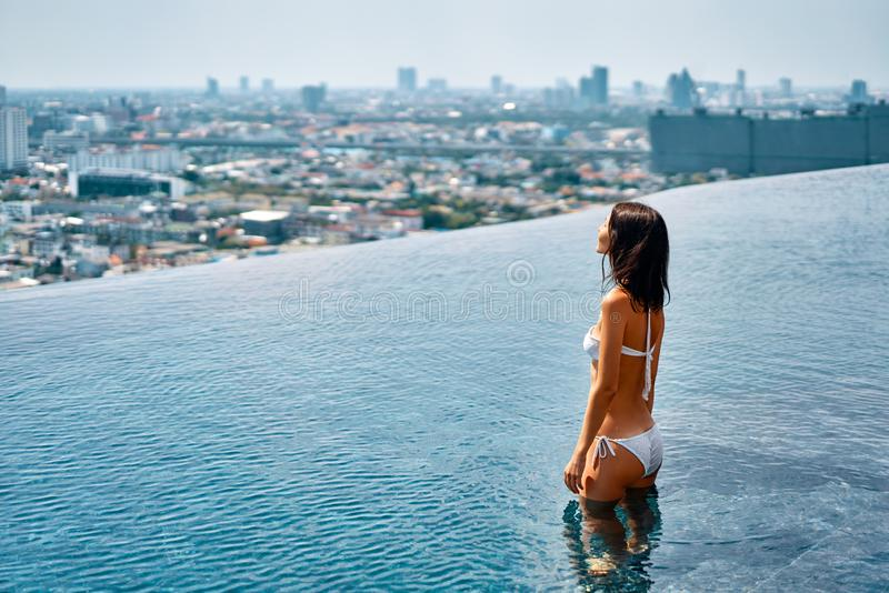 Young beautiful woman relax in swimming pool on rooftop and enjoy cityscape. Summer vacation concept stock image