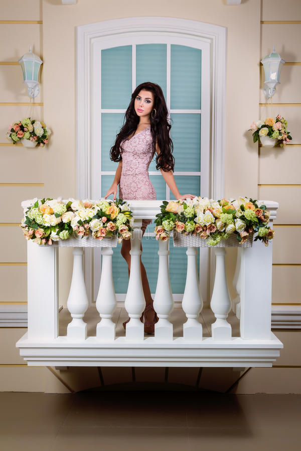 Young beautiful woman relaxing on a balcony. A beautiful woman in a dress. The picture on the balcony stock photography