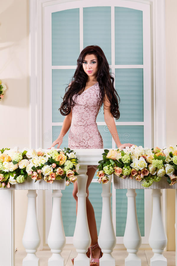 Young beautiful woman relaxing on a balcony. A beautiful woman in a dress. The picture on the balcony royalty free stock images