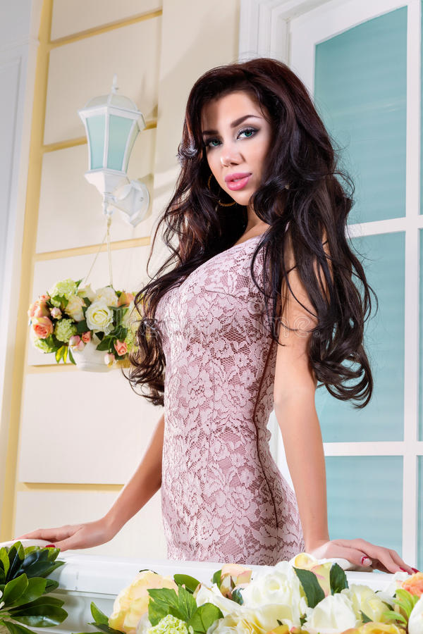Young beautiful woman relaxing on a balcony. A beautiful woman in a dress. The picture on the balcony stock photos