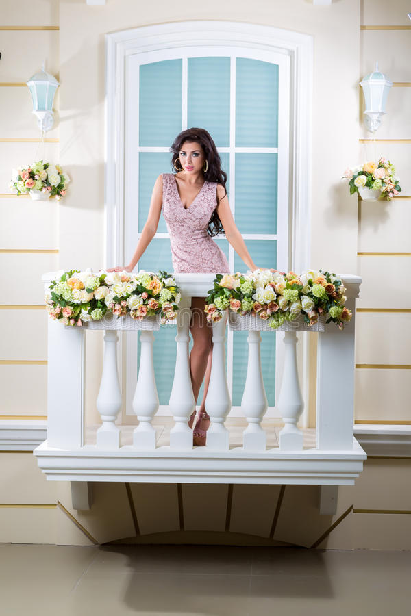 Young beautiful woman relaxing on a balcony. A beautiful woman in a dress. The picture on the balcony royalty free stock photos