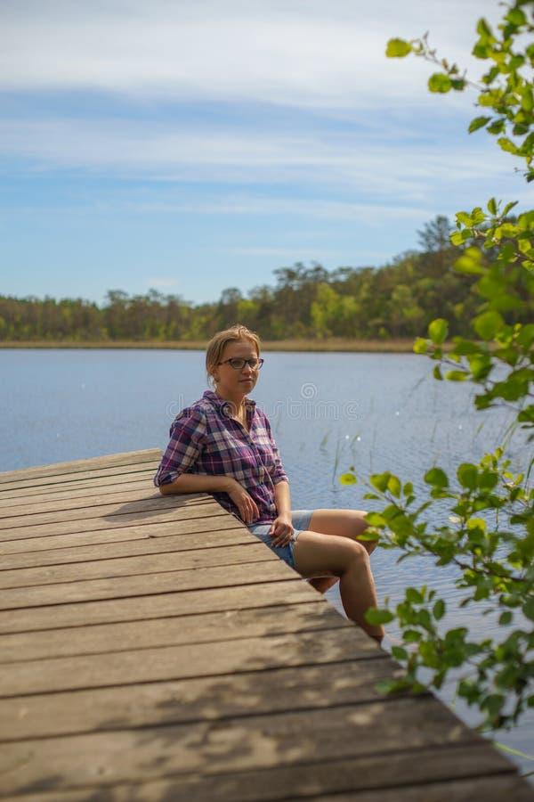 Young beautiful woman relaxing near scenic lake. Vertical view stock photo