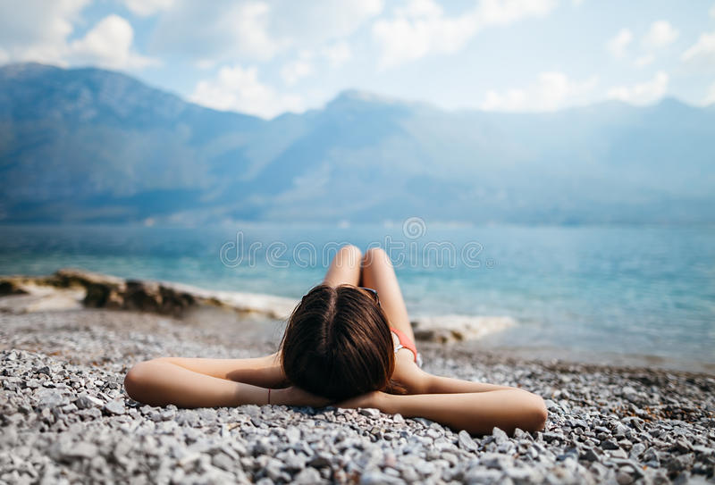 Young beautiful woman relaxing on pebble beach in beautiful Garda lake. Vacation concept royalty free stock photos
