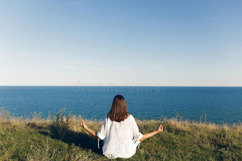 Young beautiful woman relaxing and practicing yoga on beach, sitting in grass, meditating and listening to sea waves. Hipster girl. Doing yoga. Meditation,calm royalty free stock photos