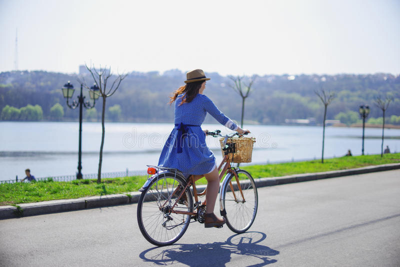 Young beautiful woman riding a bicycle in a park. Active people. Outdoors stock photography