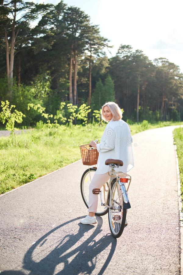 Young beautiful woman riding a bicycle in a park. Active people. Outdoors relax.  royalty free stock photography