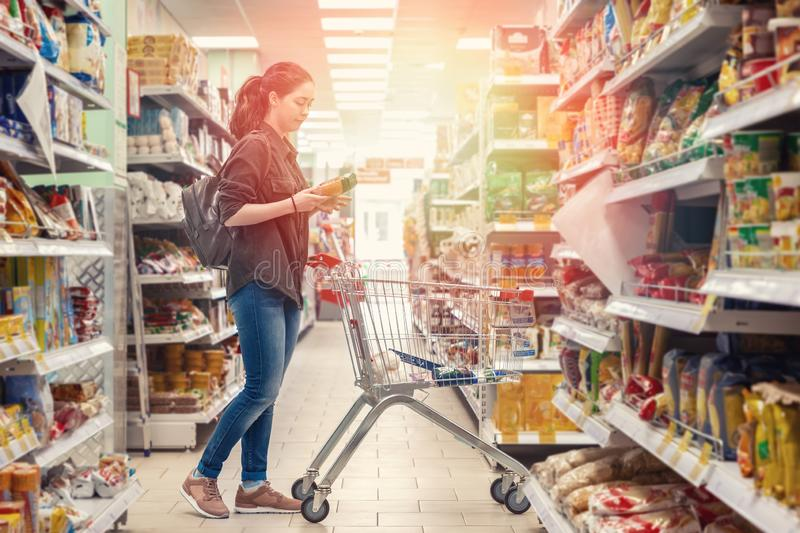 A young beautiful woman rolls a grocery cart and chooses products in the supermarket. Light stock photo