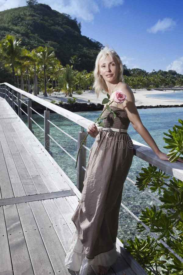 The young beautiful woman with a rose on a wooden path at the sea, tropics. Tahiti stock image