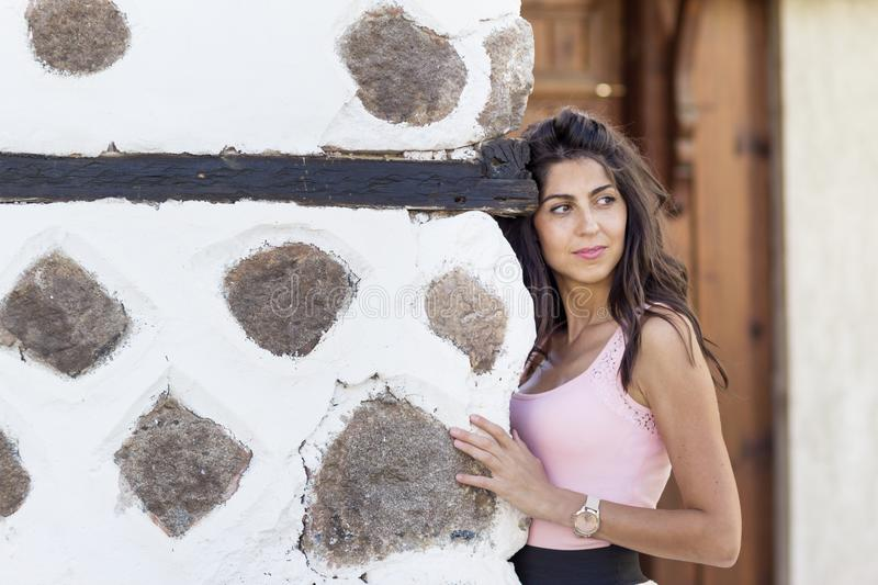 Young beautiful woman on a rustic wall. Brunette beautiful woman with curly hair royalty free stock photos