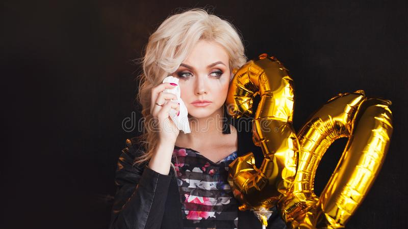 Young beautiful woman is sad on her birthday. Charming blonde crying because youth goes away royalty free stock photos