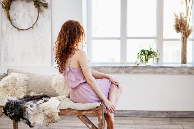 Young beautiful woman sad by the window, beautiful red hair royalty free stock photo