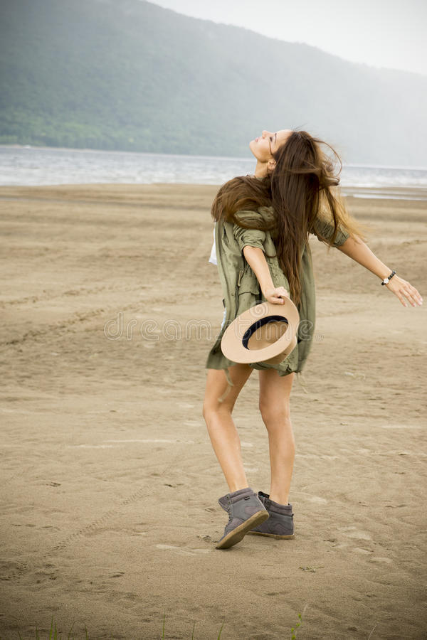 Young beautiful woman on a sandy beach stock photo