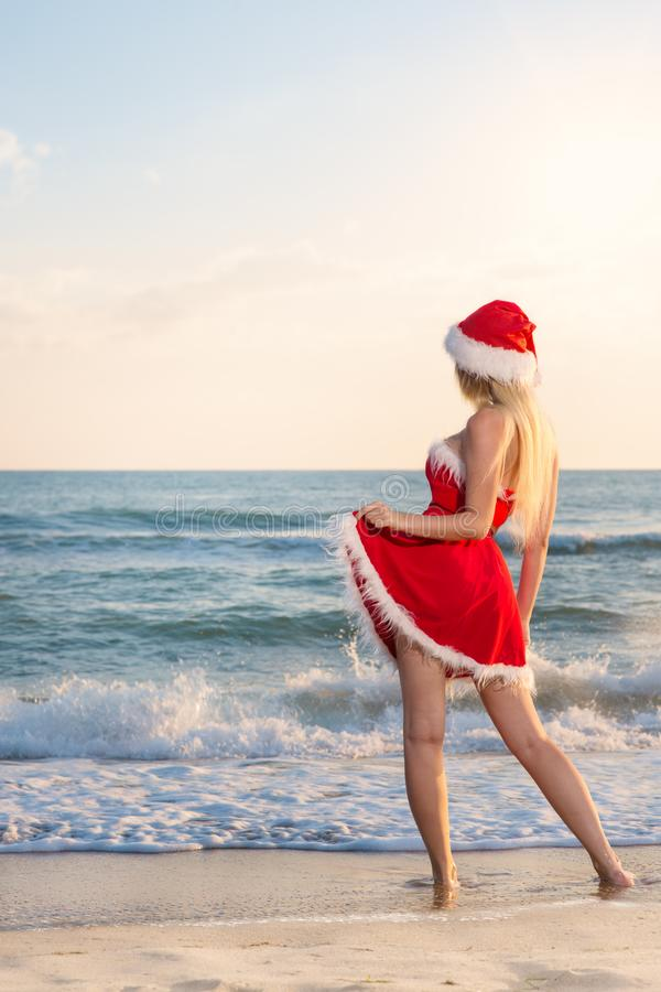 Young beautiful woman in Santa Claus costume celebrates Christmas on a trip to warm countries on the sandy beach stock image