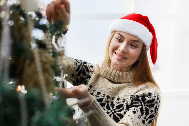 Young beautiful woman decorating christmas tree, new year decoration background stock image