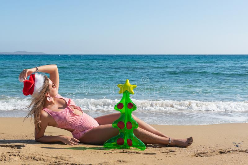 Young beautiful woman in santa hat with inflatable Christmas tree on the beach. Christmas vacation concept.  royalty free stock image