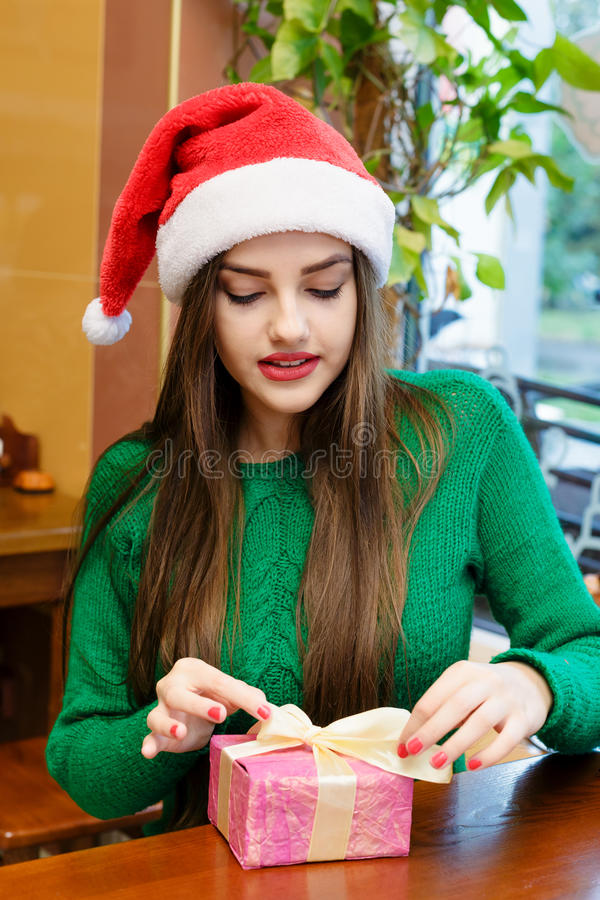 Young beautiful woman in santas hat opening gift box royalty free stock images