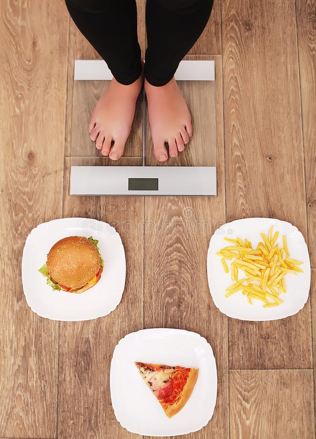 A young beautiful woman is on the scales. To choose between potato chips, pizza and burgers. The concept of healthy eating. Health. Y Lifestyle. Diet royalty free stock images