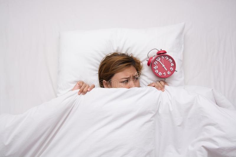 Young beautiful woman scared alarm clock to wake herself in the stock photography