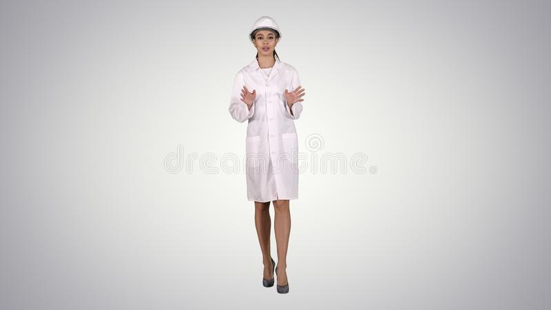 A young beautiful woman scientist engineer in white giving lecture on gradient background. stock photo