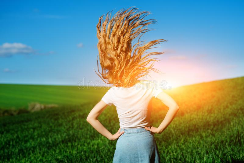 Young beautiful woman is shaking her hair on greenfield from the stock photo