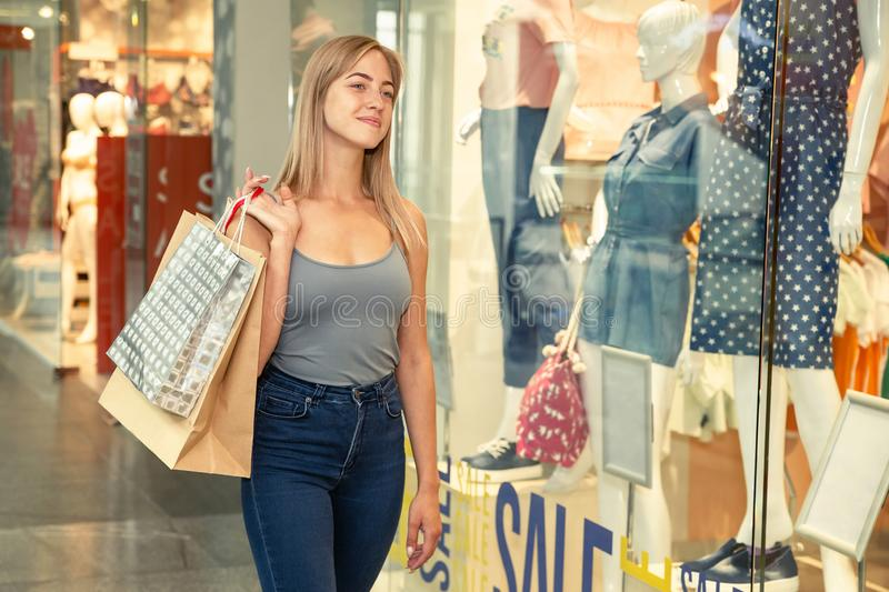 Young beautiful woman on shopping in the mall holds shopping bags in hands. Fashion, clothing, sale, discount concept stock images