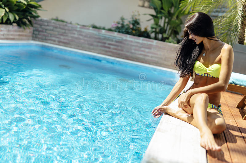 Young beautiful woman on the side of the pool playing with water. Displaying sensuality royalty free stock images