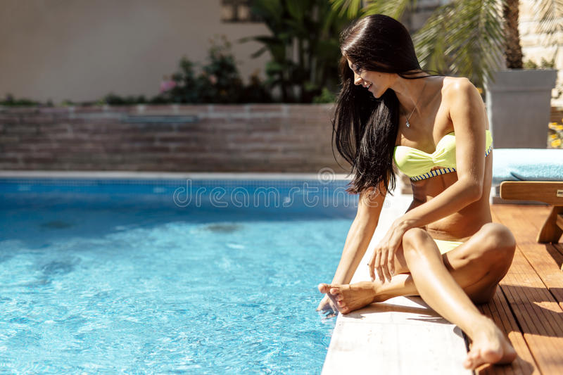 Young beautiful woman on the side of the pool playing with water. Displaying sensuality stock images