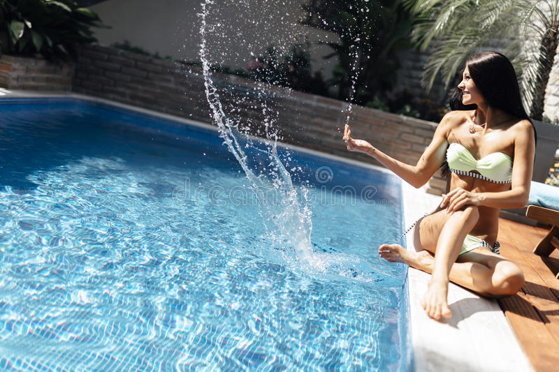 Young beautiful woman on the side of the pool playing with water. Displaying sensuality stock photo