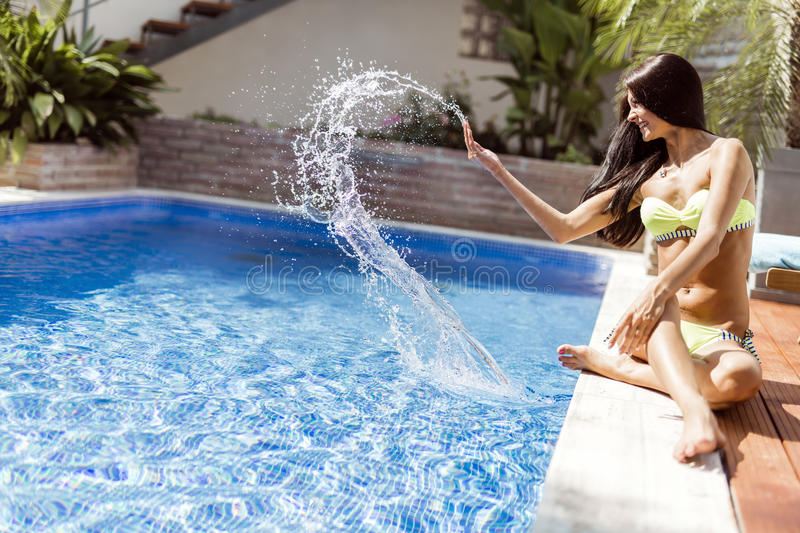 Young beautiful woman on the side of the pool playing with water. Displaying sensuality royalty free stock photos