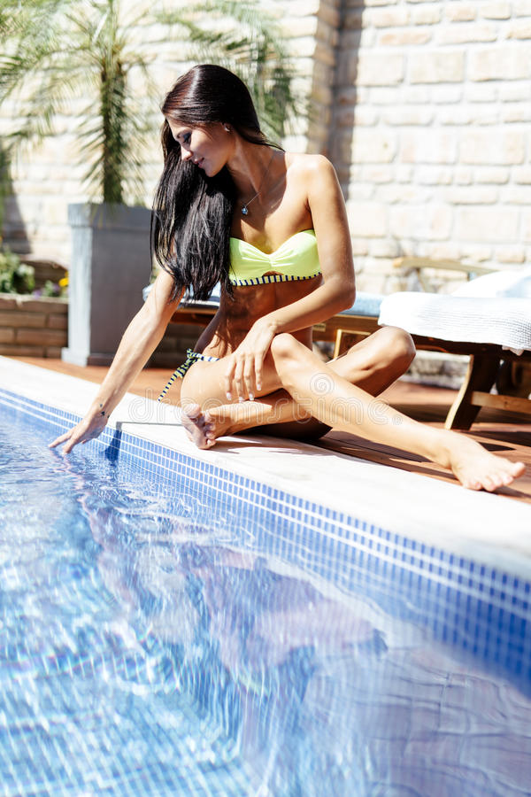 Young beautiful woman on the side of the pool playing with water. Displaying sensuality stock photos