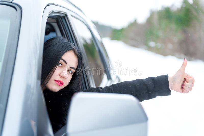 Young beautiful woman signaling problems with broken car on win royalty free stock photo