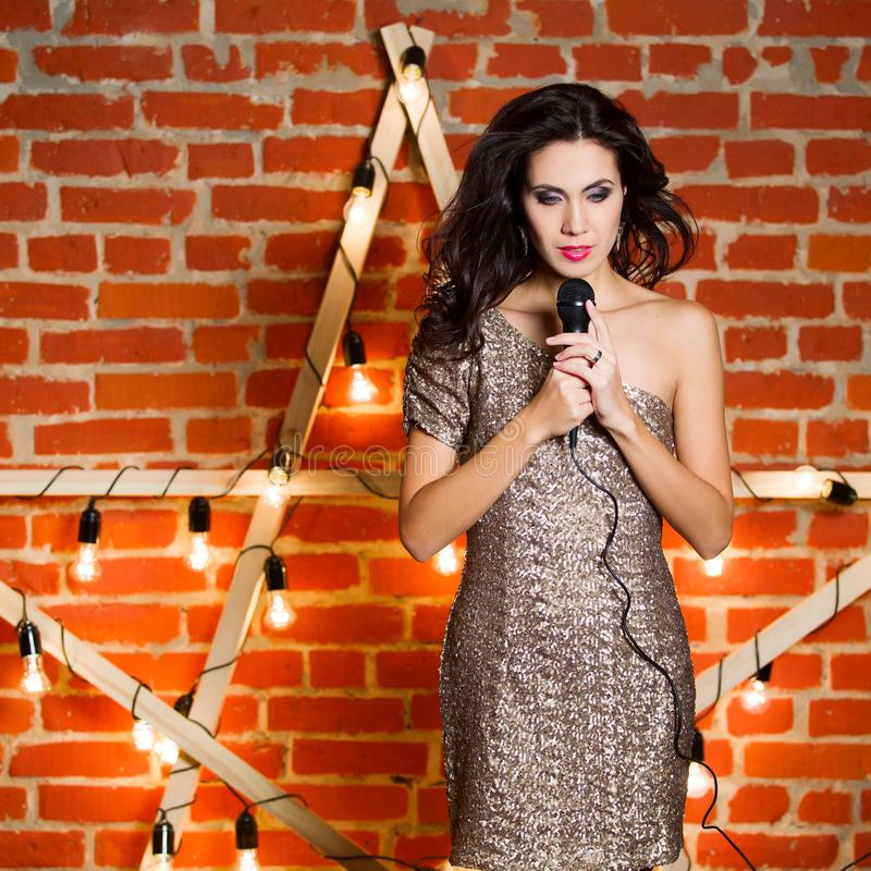 Young beautiful woman singing song over wooden star with bright stock photo