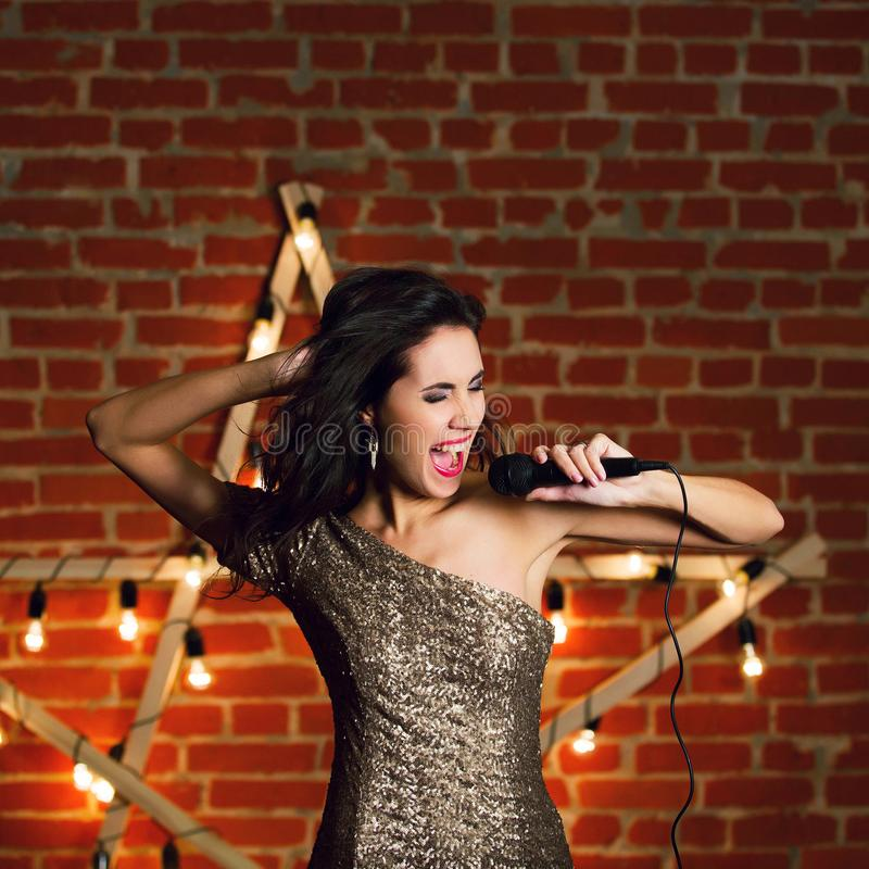 Young beautiful woman singing song over wooden star with bright royalty free stock photography