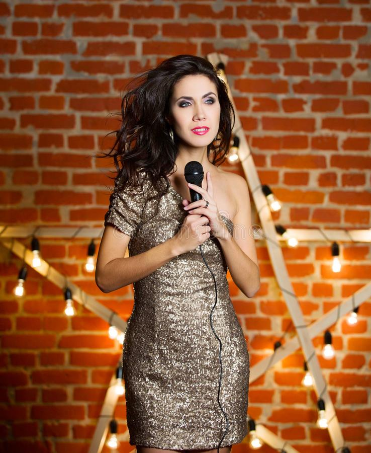 Young beautiful woman singing song over wooden star with bright royalty free stock images