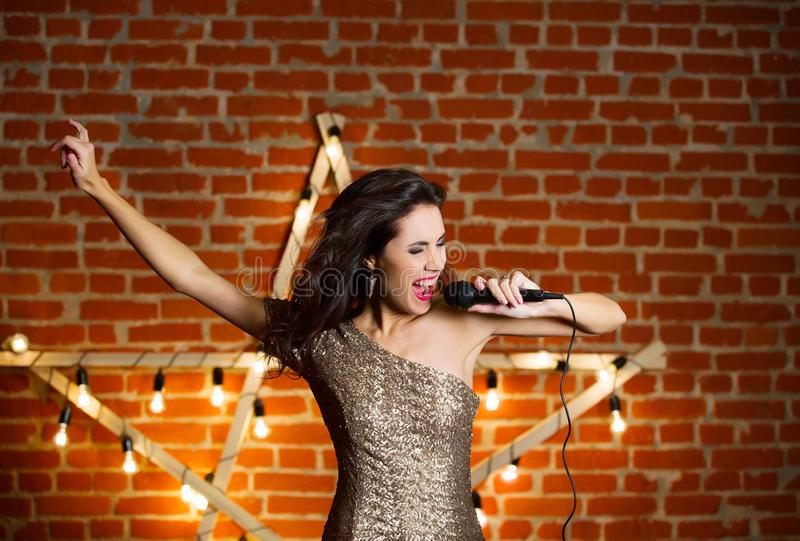 Young beautiful woman singing song over wooden star with bright stock photography