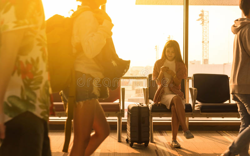 Young beautiful woman sit in airport with travel bag use smartphone at airport wait for flight, world exploration concept stock photo