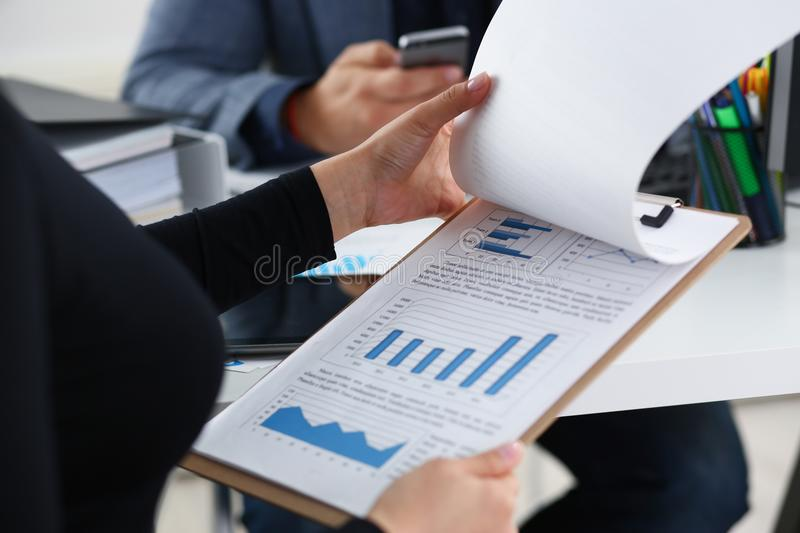 Young beautiful woman sit on chair at table in office in cabinet of her boss hold binder in arms closeup royalty free stock images