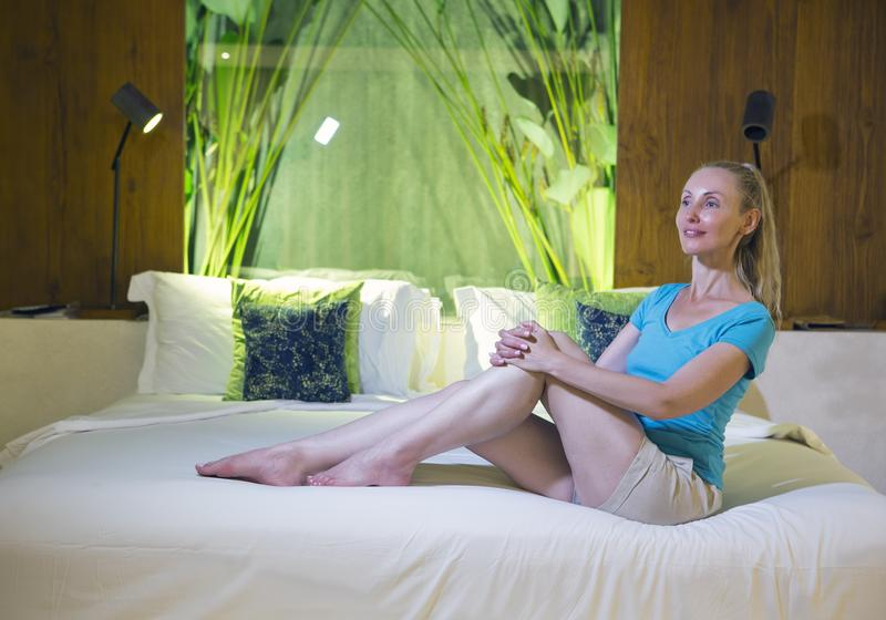 The young beautiful woman sits on big bed with throw pillows stock image
