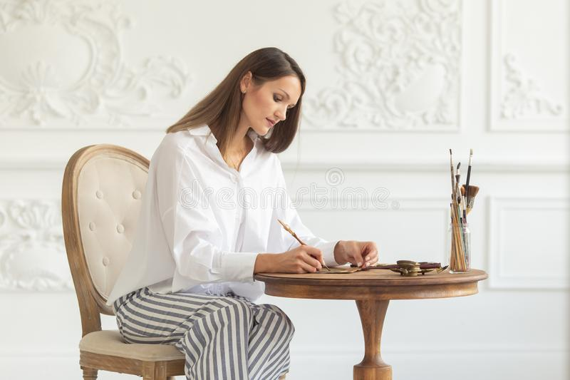 A young beautiful woman sits on a chair in the luxurious interior of a living room and writes a letter. Romantic mood royalty free stock images