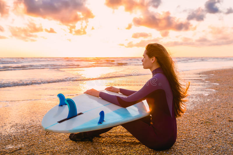Young beautiful woman is sitting on the beach. Surf girl with surfboard on beach at sunset or sunrise. Surfer and ocean. Sporty surf girl go to surfing. Woman stock photo