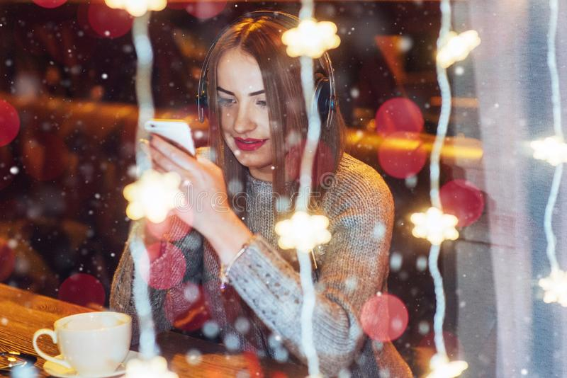 Young beautiful woman sitting in cafe, drinking coffee. Model listening to music. Christmas, Happy new year, Valentines day, winte stock image