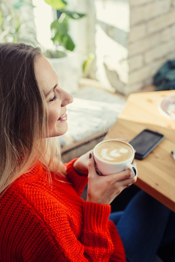 Happy woman enjoying cappuccino coffee in a cafeteria stock image