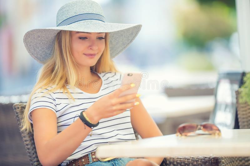 Young beautiful woman sitting in cafe and using smartphone. Coffee, lifestyle, girl, mobile, people, female, business, portrait, internet, happy, restaurant stock photo