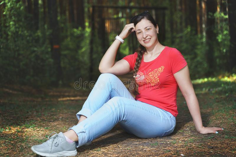 Young beautiful woman sitting on the floor and feeling happy. She is wearing casual clothes royalty free stock image