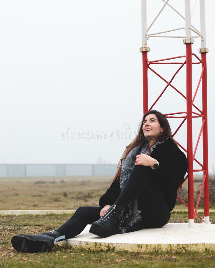 Young beautiful woman sitting on the floor in an small airport looking up in a small airport in a rural landscape. Attractive royalty free stock photo