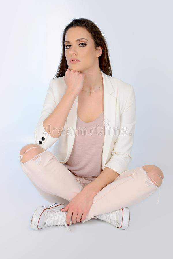 Young beautiful woman sitting on the floor, wearing white jacket and jeans stock photo